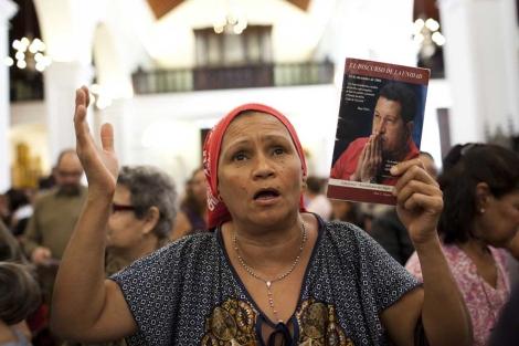 Una seguidora de Chávez participa de una misa masiva por la recuperación del líder venezolano. | Reuters