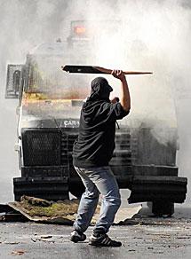Un manifestante se enfrenta a la Policía. | Efe
