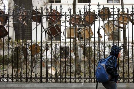Un estudiante camina junto a una reja en la que se observan sillas colgadas. | Efe