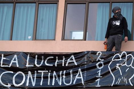 Un joven manifestante coloca un cartel en el centro de Santiago. | Efe