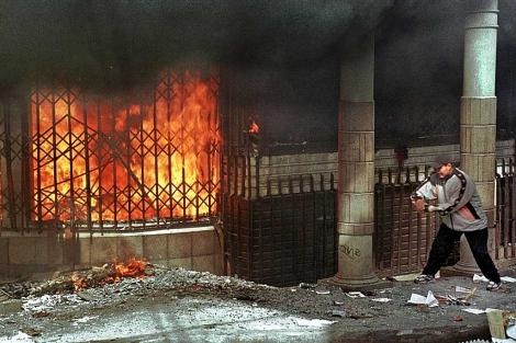 Un hombre intenta entrar en un edificio incendiado durante las protestas de 2003 en Bolivia. | AFP