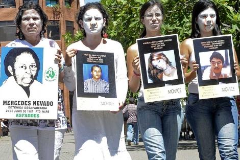 Activistas y familiares muestran fotografías de desaparecidos. | AFP