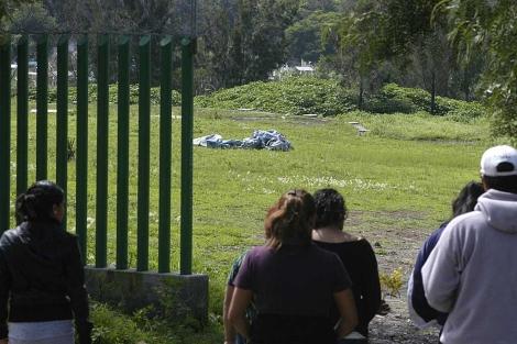 Varias personas observan la manta que cubre los cuerpos de las periodistas asesinadas. | Efe