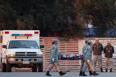 Oficiales de las fuerzas aéreas de Chile trasladan uno de los cuerpos. | Ap