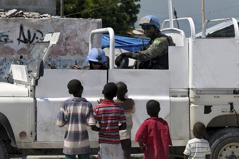 Dos cascos azules de la ONU hablan con varios niños haitianos. | Reuters