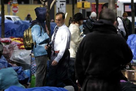 Un hombre de negocios pasa entre los 'indignados' de Zuccotti Park.   Ap