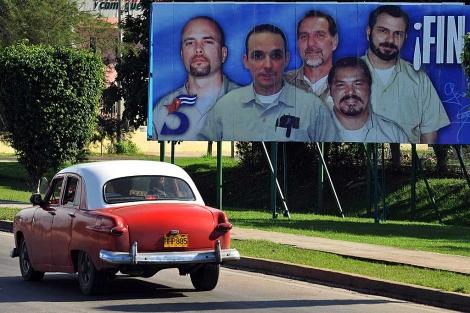 Un vehículo pasa en La Habana por un cartel alusivo a los cinco cubanos. | Efe