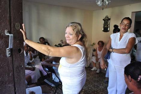 Laura Pollán (c) mira fuera de una casa donde se reúnen las Damas de Blanco. | AFP