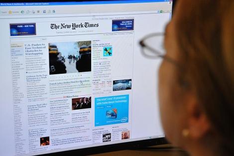Una mujer lee la página en Internet de The New York Times. | AFP
