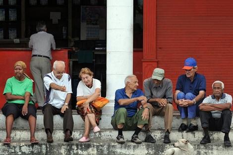 Un grupo de ancianos conversa frente a una bodega en La Habana. | Efe