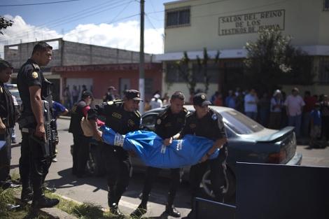 Varios policías guatemaltecos retiran un cadáver de la escena del crimen. | AP