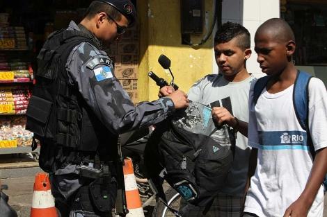 Un policía registra las mochilas de dos jóvenes negros en la favela Rocinha. | Efe