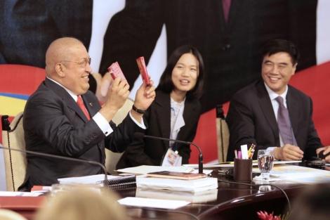 Hugo Chávez (i) celebra con dos copias del libro de Mao Zedong durante una reunión con el vice ministro chino Zhang Xiaoqiang (d).   Reuters