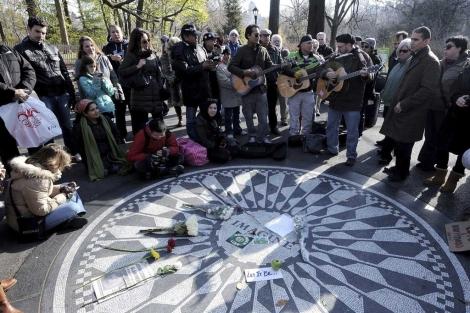 Un grupo de personas toca canciones de John Lennon junto al monumento en Central Park. | Efe