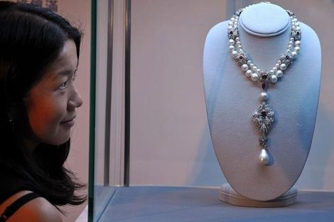 Una mujer observa la gargantilla con la perla llamada 'La Peregrina'. | AFP