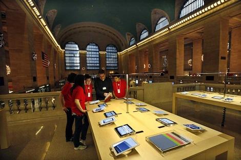 Empleados de Apple observan un iPad en una tienda de Nueva York. | Reuters