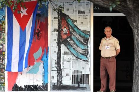 Un vigilante permanece junto a la entrada de un edificio adornada con banderas de Cuba. | Efe