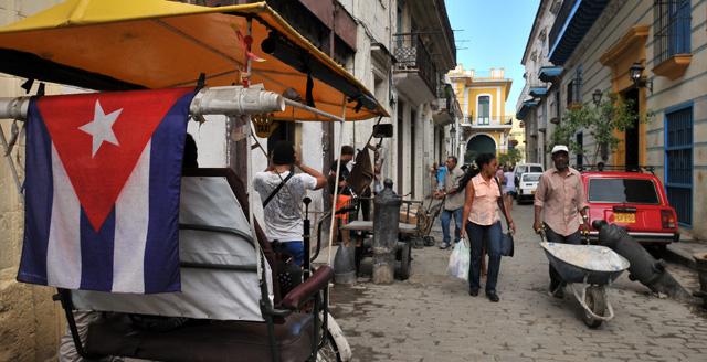 Un hombre empuja una carreta mientras conversa con una mujer en La Habana. | Efe