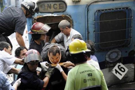 Los bomberos rescatan a un pasajero del vagón.| Reuters (VEA MÁS FOTOS)