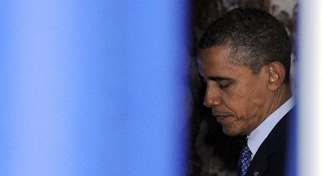 Obama espera tras las cortinas antes de dar un discurso.| Afp