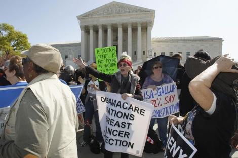 Varias personas se manifiestan en contra de la reforma de Obama. | Reuters