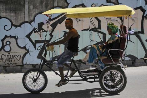 Un hombre lleva a una mujer en su triciclo-taxi en La Habana. | Reuters