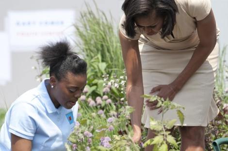 Michelle Obama regando unas plantas.| Afp