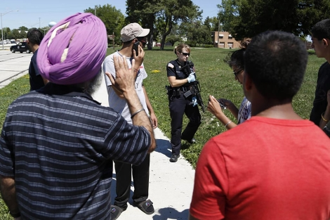 Vecinos y familiares se mezclan con los policías a las afueras del templo.| Afp