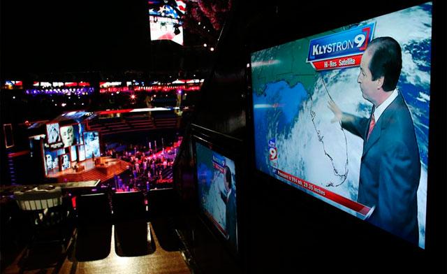 Una pantalla de televisión informa de la tormenta en la convención. | Afp