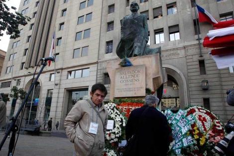 Unos chilenos ponen flores en la estatua de Allende.| Reuters