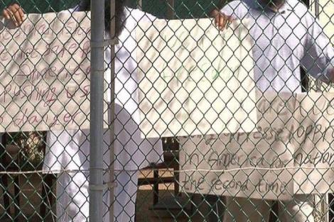 Dos reclusos con carteles de protesta en Guantánamo. | EL MUNDO
