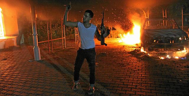 Un hombre armado ante el incendio del consulado en Bengasi, en el que murió el embajador. | Afp