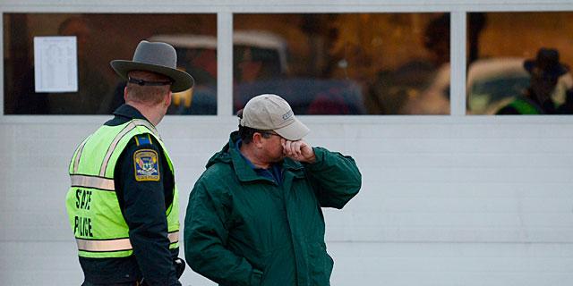 Un hombre llora, junto a un policía ante el cuartel de bomberos donde llevaron a los niños tras la masacre. | Efe/EPA