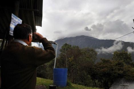 Carlos Sánchez, observa el volcán desde la estación del Instituto Ecuatoriano de Geofísica.   Afp