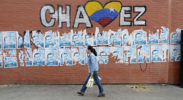 Una mujer pasa por una zona con carteles de apoyo a Hugo Chávez.   Afp