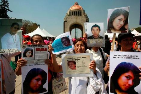 Un grupo de mujeres sostiene fotografías de desaparecidos.   Efe