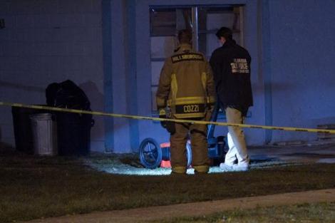 Dos técnicos realizan exámenes al suelo alrededor de la casa. | Tampa Bay Times