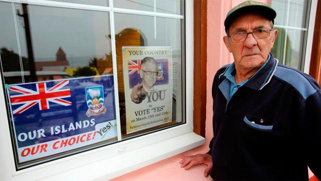 Un habitante de las islas junto un cartel del referéndum.   Afp