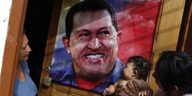 Un niño besa un póster de Chávez.| Reuters