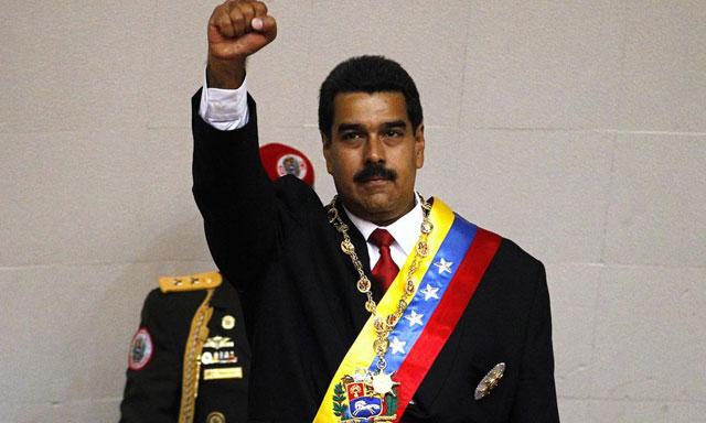 Maduro con el puño en alto y la banda presidencial.| Reuters
