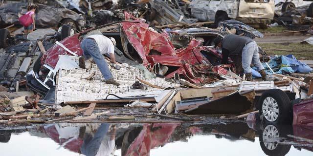 Vecinos de Oklahoma buscan entre los restos de un vehículo.   Efe