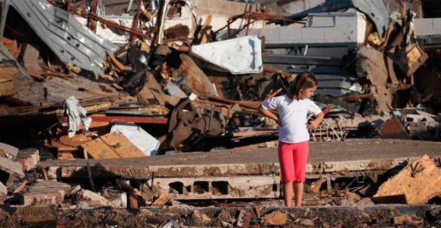 Una niña mira su casa destrozada por el tornado.   Afp