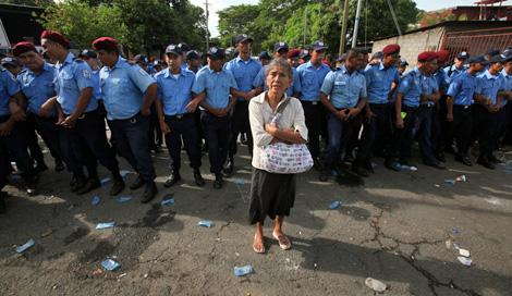 Una anciana protesta frente a un grupo de policías. | Efe