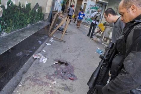 Dos agentes ante la escena del crimen en la favela Nova Holanda.  Afp