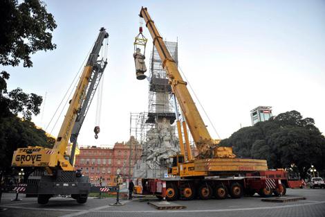 Dos grúas trabajan en la retirada del monumento.   Efe