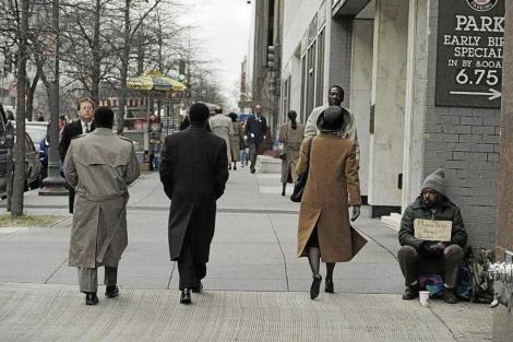 Un grupo de personas pasean ante un mendigo en Washington.   Mark Wilson