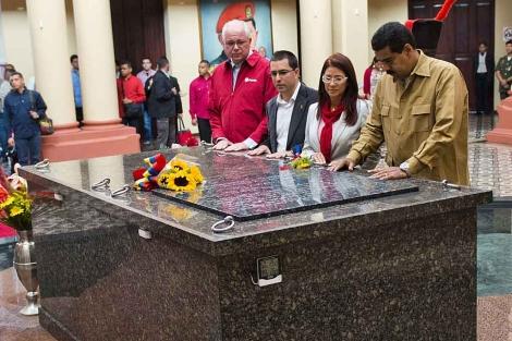 Maduro; su esposa, Cilia Flores, y el vicepresidente Arreaza, ante la tumba de Chávez. | Afp