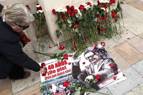 Una mujer deposita flores en el monumento a Allende. | Efe