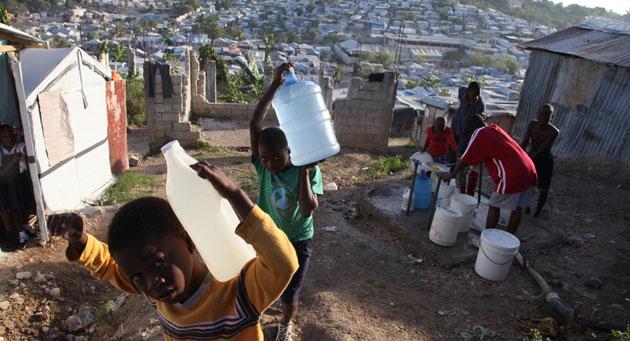 Un grupo de niños carga con bidones de agua en Delmas, Puerto Príncipe. | Unicef