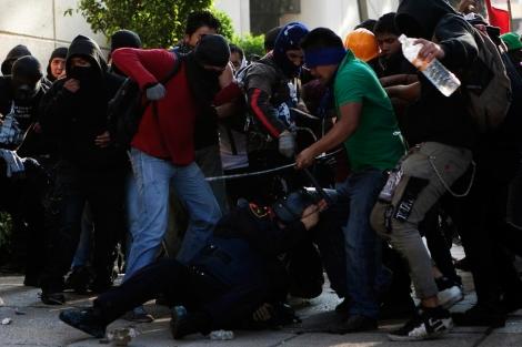 Manifestantes patean a un agente antidisturbios durante la marcha.   Reuters